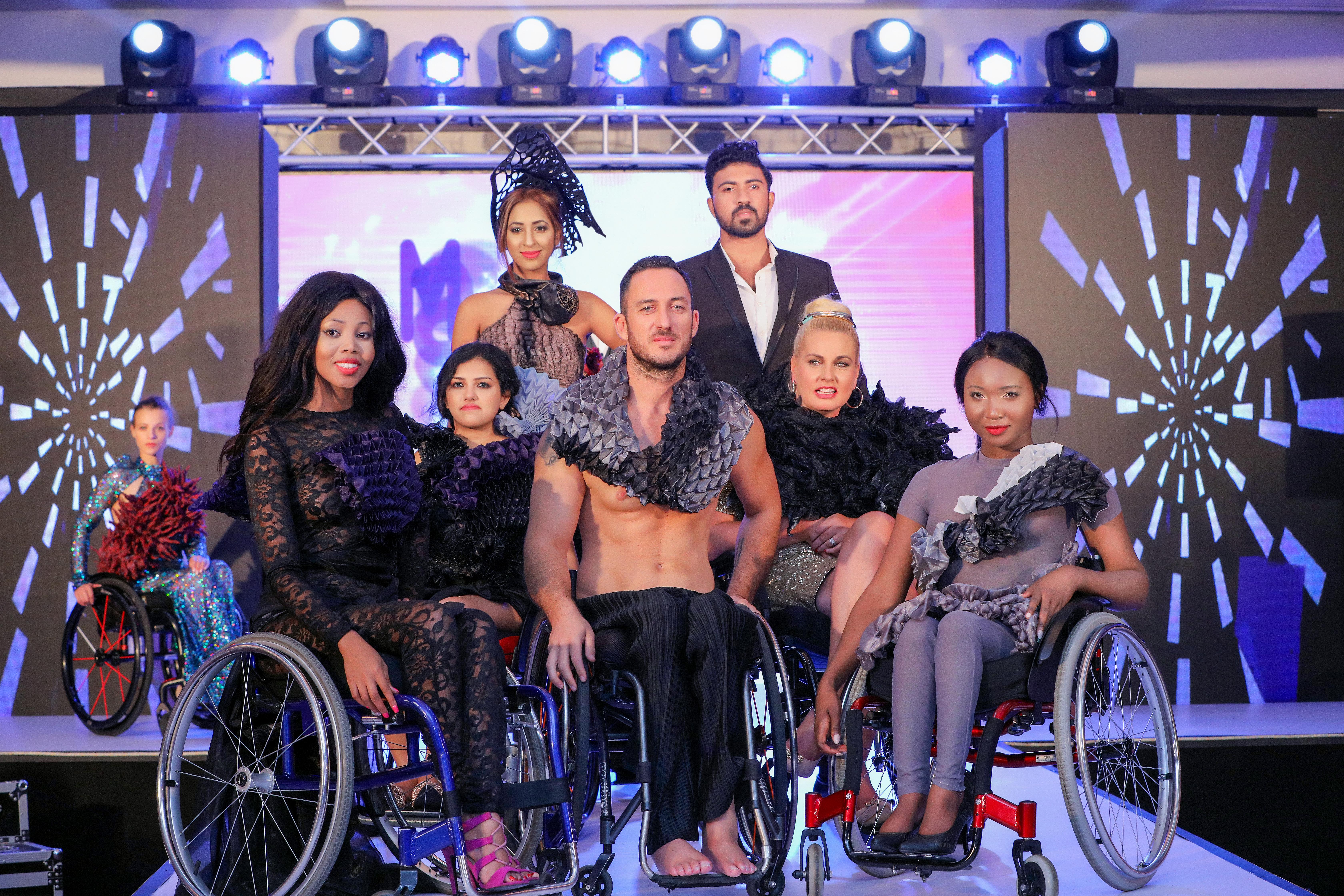 Photo de 8 mannequins présents au défilé de mode, sur le podium. 7 sont au premier plan, une est à l'arrière plan. De gauche à droite :  Première mannequin au fond à gauche est assise sur un fauteuil roulant, ses cheveux sont tirés attachés, elle porte une robe bleu longue pailletée avec un châle rouge et noir.  La deuxième mannequin, assise sur un fauteuil roulant, a les cheveux noirs, porte une combinaison en dentelle noire, des sandales à talons rose fushia, et un rouge à lèvres rouge.  La 3ème mannequin en fauteuil roulant a les cheveux bruns, on devine juste une tenue noire.  La 4ème mannequin est debout à l'arrière, elle porte un chapeau noir et une robe beige et noire.  Le 5ème mannequin est un homme torse nu sur un fauteuil, il est blond foncé barbu plutôt musclé. Il porte un châle gris et noir et un pantalon noir.  Le 6ème mannequin est un homme debout à l'arrière en costume noire et chemise blanche, brun et barbu.  La 7ème mannequin porte une robe dorée, elle est sur un fauteuil roulant, cheveux blonds tirés en chignon.  La 8ème mannequin a les cheveux noires attachés, elle est en fauteuil roulant et porte une combinaison manches courtes grise près du corps, des escarpins noir, etun châle gris, blanc et noir.