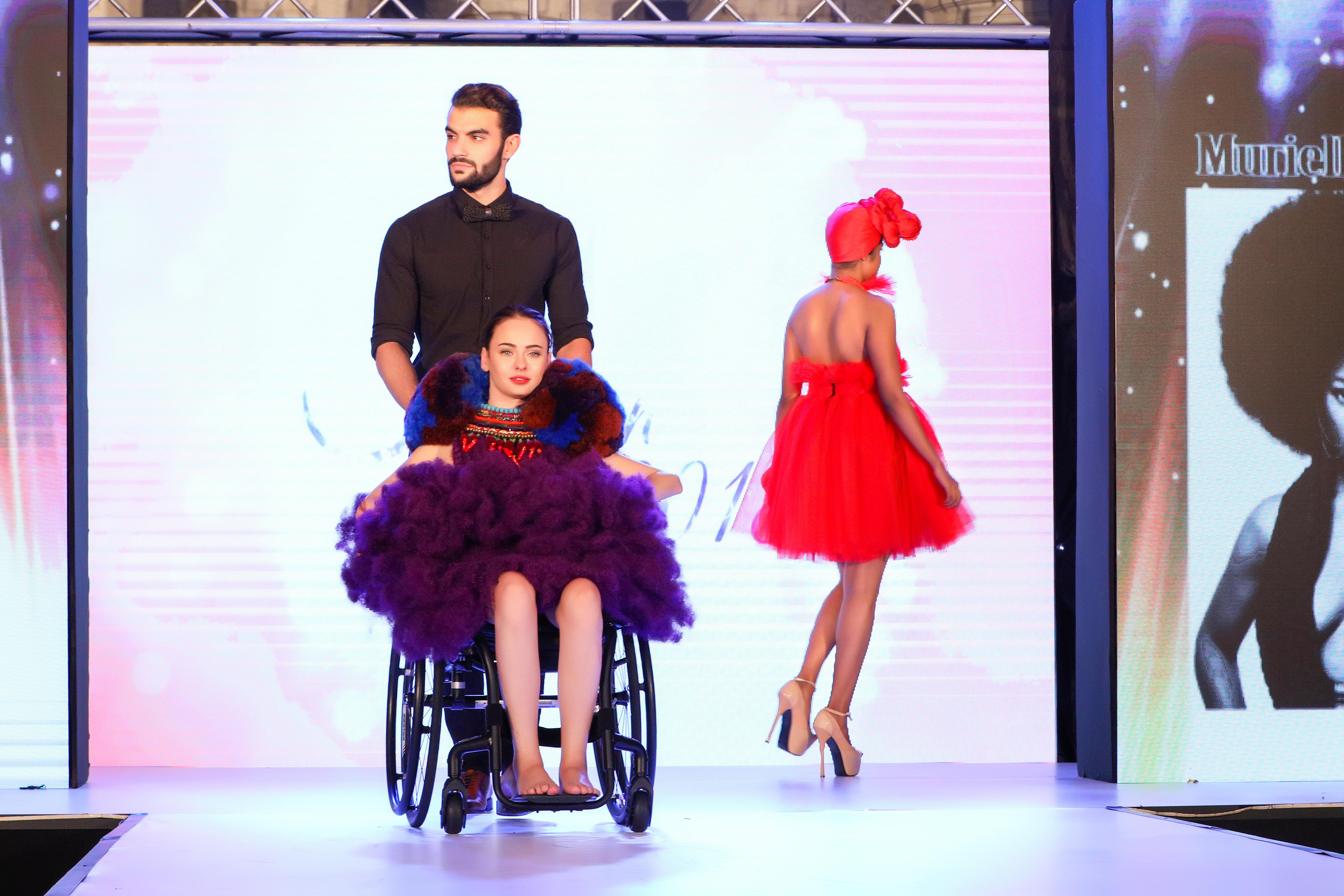 Photo prise lors du défilé de mode sur le podium. 3 personnes défilent avec les tenues des créateurs.  La première est de dos, c'est une femme qui marche vers les coulisses, elle porte une robe rouge bustier courte, façon princesse, et un chapeau rouge avec un noeud sur le devant. Elle porte des escarpins rose clair avec de très haut talons.  Une deuxième femme est sur un fauteuil roulant poussé par un homme vêtu d'une chemise et d'un noeud papillon noirs. Il est barbu. La jeune femme a des yeux bleus et les cheveux attachés bruns. Elle porte une robe façon tutu de danseuse, violette, avec des colliers colorés et de la fausse fourrure autour du cou.