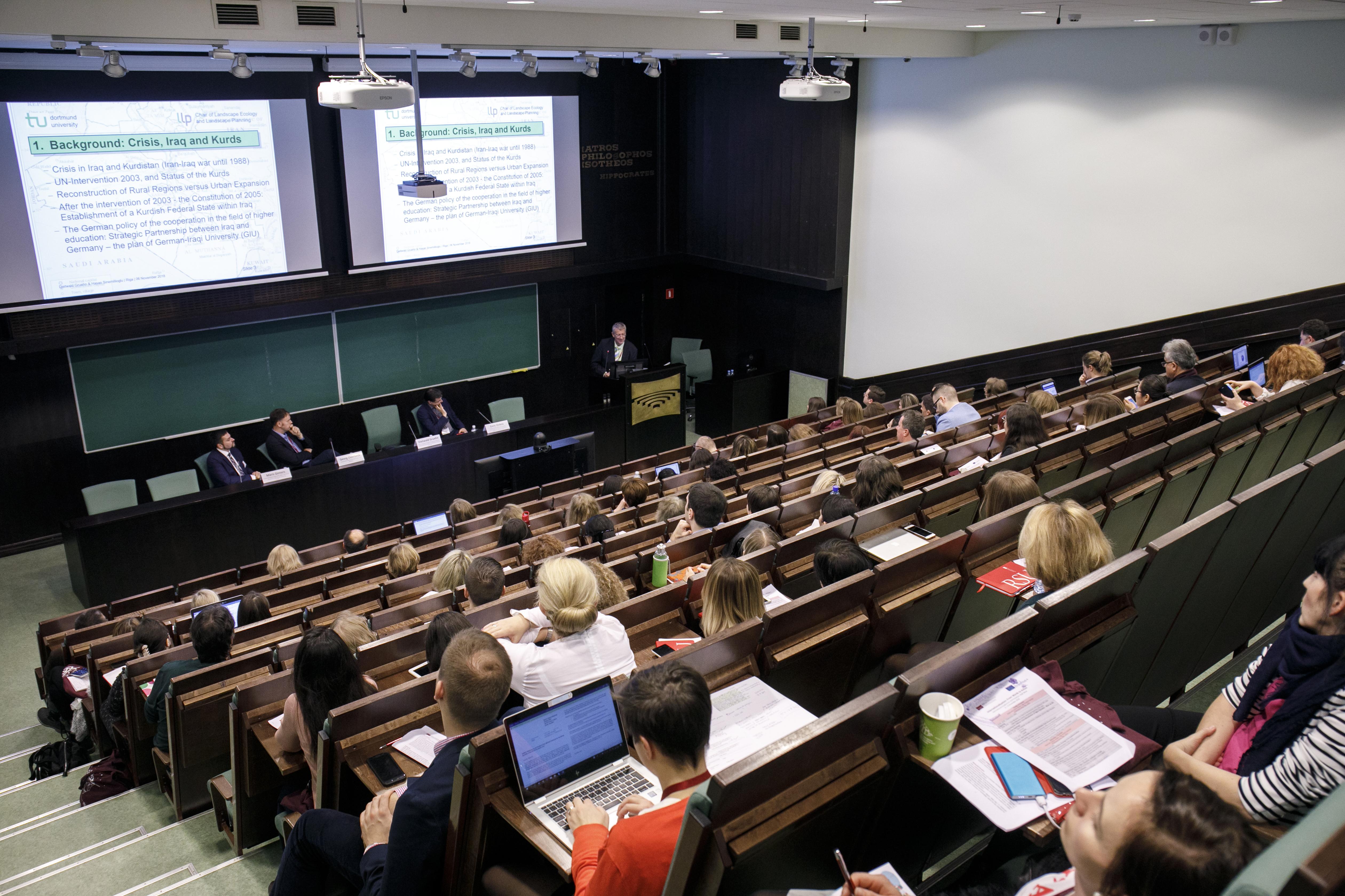 Photo d'une conférence de la semaine dans un amphithéâtre. Des diapositives sont projetées sur le mur, il y a 4 intervenants dont 1 derrière un pupitre. La photo est prise du haut de l'amphithéâtre.