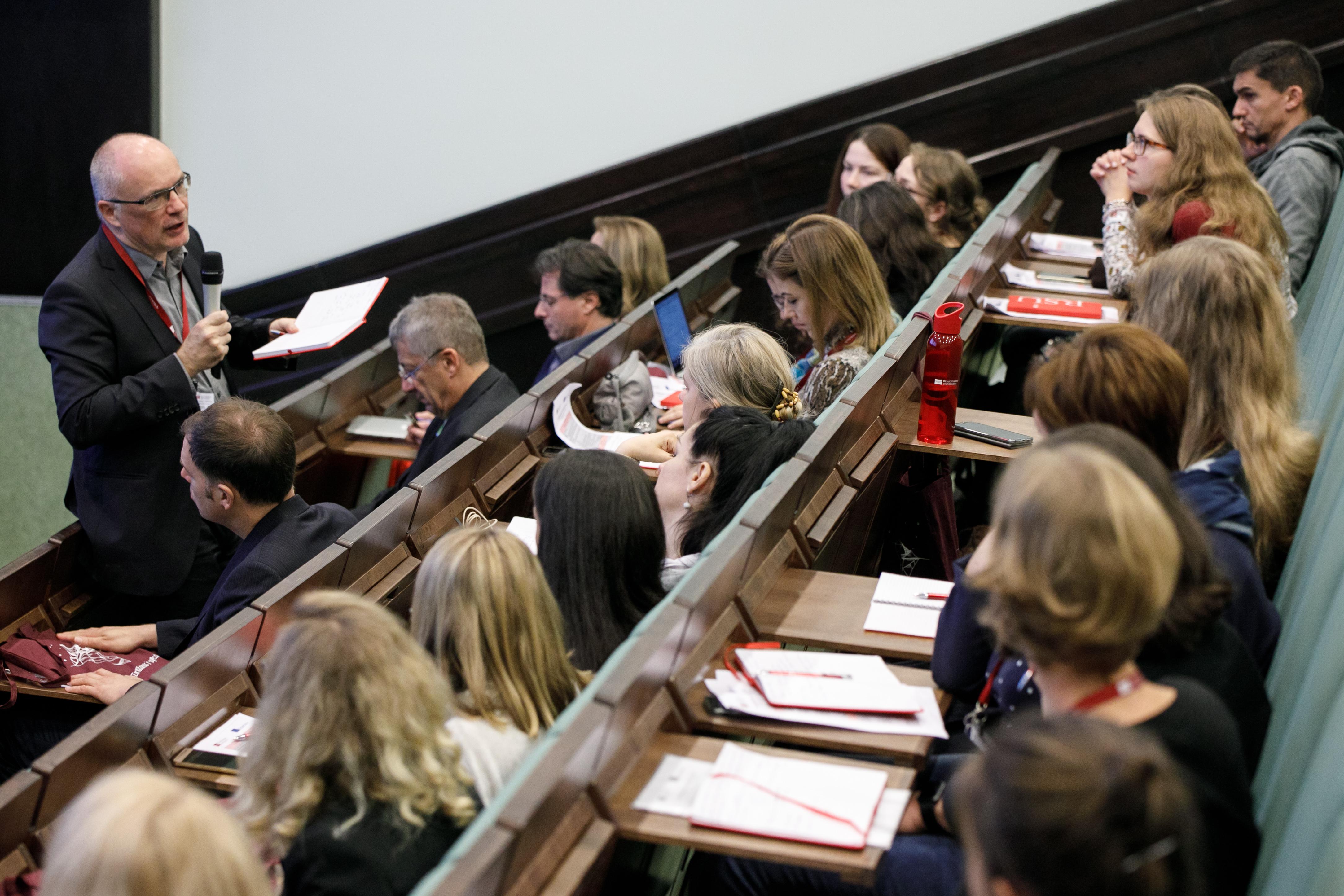 Photo prise lors d'une conférence dans un amphithéâtre. Un homme avec des cheveux blancs et lunettes s'exprime au micro tout en tenant un cahier. Nous voyons quelques personnes assises aux rangées de devant qui suivent la conférence.