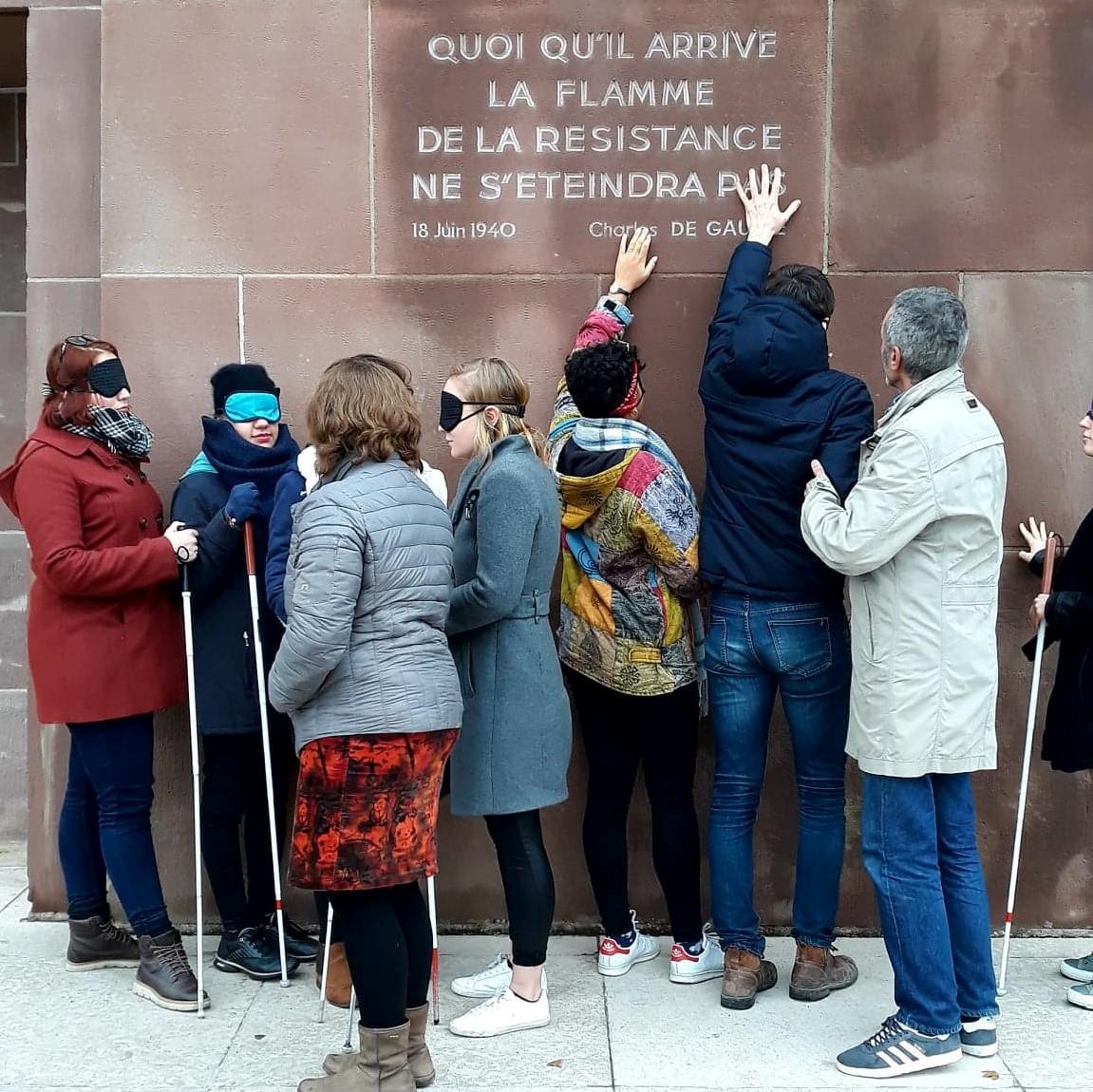 """Photo représentant 7 personnes à l'extérieur du Mémorial lors de l'exercice de mise en situation de déficience visuelle. Ils ont des cannes blanches et des bandeaux sur les yeux, et touchent avec les doigts les écritures sur le mur du Mémorial : """" Quoi qu'il arrive la flamme de la résistance ne s'éteindra pas """"."""