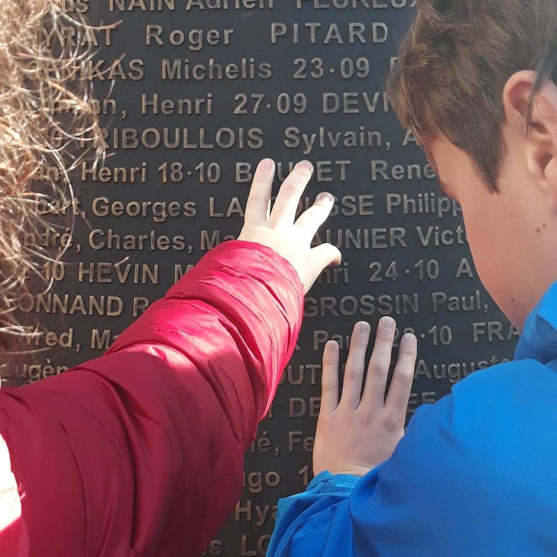 Photo de 2 enfants de dos touchant les écritures en relief des noms des résistants et otages fusillés du Mont-Valérien.