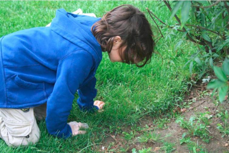 élève à genou dans l'herbe et qui observe le sol
